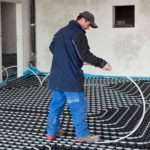 Heating Engineer Installing Wet Undefloor Pipes Into Large